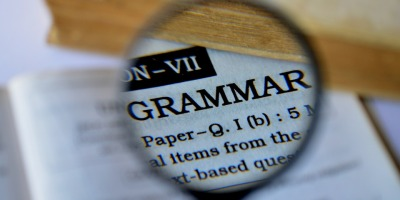 "A magnifier placed over a book, focusing on the word ""grammar."""