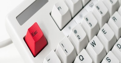 Close up of the top left of a keyboard. The escape key is colored red.