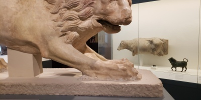 "Horizontal, beige lion sculpture at an art museum. Below the sculture is a sign that says ""please do not touch."